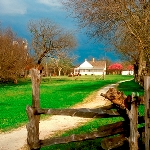 Picture of Penn Farm, with a wooden fence in front of a dirt path, leading to the farm in the distan