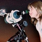 Little girl gazes through a special telescope to get a better view of stars..jpg